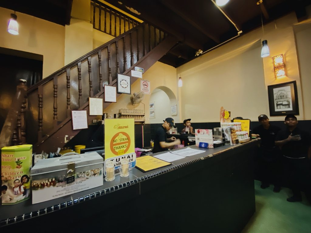 Ipoh Hainan's cashier counter below the stairs with some standing crews